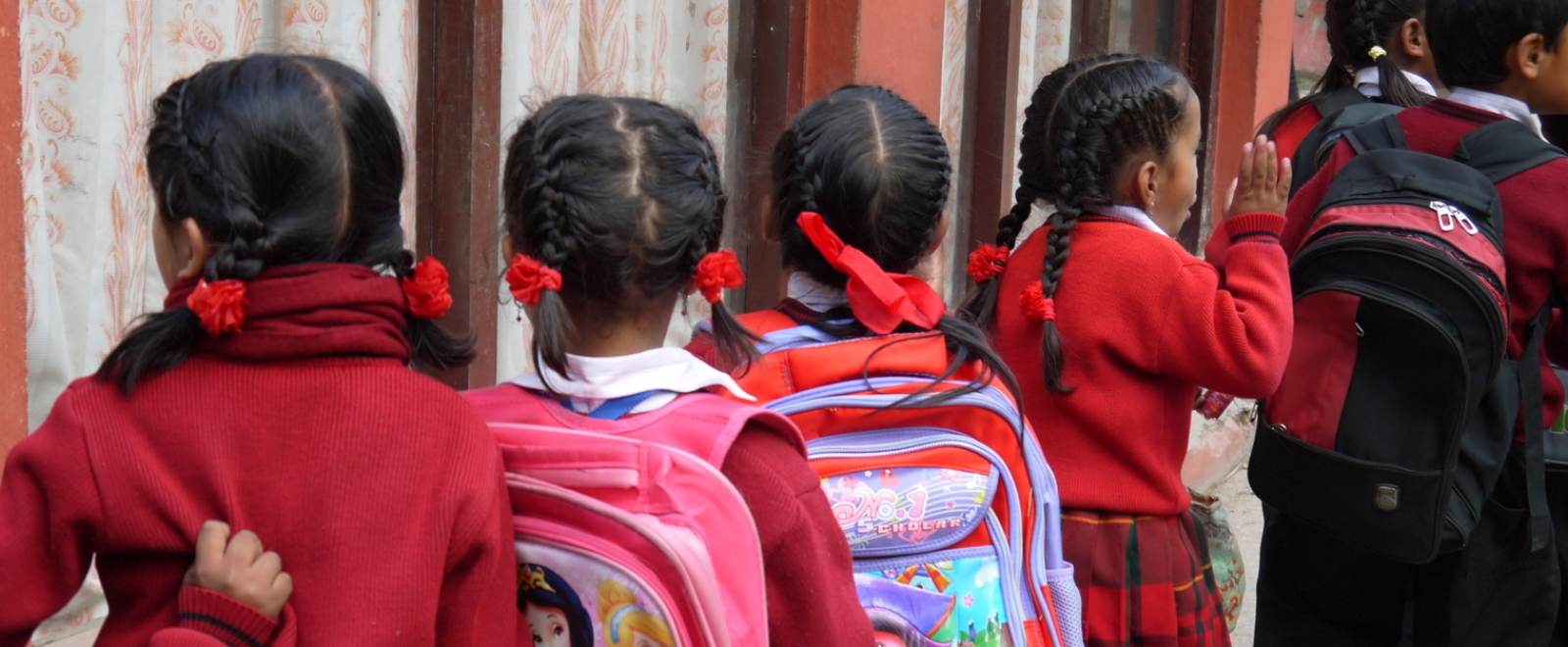 Children line up with their backpacks outside their classroom in Nepal